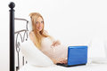 Pregnancy woman with laptop in bed at home Royalty Free Stock Images