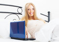 Pregnancy woman with laptop in bed long haired Stock Photo