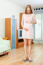 Pregnancy woman standing on bathroom scales at home Stock Photography