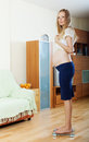 Pregnancy woman standing on bathroom scales serious at living room Royalty Free Stock Images