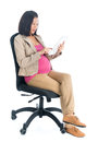 Pregnant asian business woman using digital computer tablet pc full body six months sitting on chair isolated on white background Stock Photo
