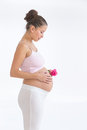 Pregnant asian woman with a rose in hands on her belly isolated against white background and Royalty Free Stock Image