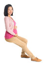 Pregnant asian woman sitting full body six months on invisible chair looking at camera isolated on white background Stock Photo