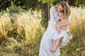 Pregnant beautiful mother with little blonde girl in a white dress sitting on a swing, laughing, childhood, relaxation Royalty Free Stock Photo