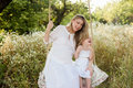 Pregnant beautiful mother with little blonde girl in a white dress sitting on a swing, laughing, childhood, relaxation
