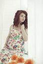 Pregnant beautiful red haired woman sitting on a window sill at the window cute Royalty Free Stock Photography