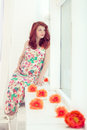 Pregnant beautiful red haired woman sitting on a window sill at the window cute Royalty Free Stock Photos