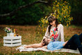 Pregnant beautiful woman with her handsome husband sweetly resting outdoors in the autumn on picnic. Royalty Free Stock Photo