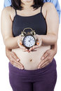 Pregnant belly and husband holding clock women her standing in studio while a Royalty Free Stock Image