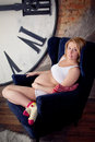 Pregnant blonde woman  near huge clock-face, big watch Stock Image