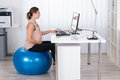 Pregnant Businesswoman On Fitness Ball Looking At Graph Royalty Free Stock Photo