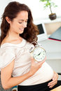 Pregnant businesswoman holding an alarm clock Royalty Free Stock Photo