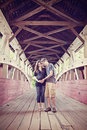 Pregnant couple on covered bridge a young in a rural setting an old Stock Photos