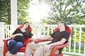 Pregnant couple relaxing an expecting women and her husband sitting on a porch holding hands Royalty Free Stock Image