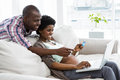 Pregnant couple shopping online on laptop at home Royalty Free Stock Photo