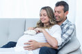 Pregnant couple sitting on sofa with baby shoes belly in living room Royalty Free Stock Photos