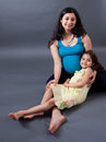 Pregnant east indian woman with her daughter portrait of a smiling women sitting Royalty Free Stock Photo
