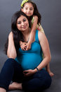 Pregnant east indian woman with her daughter portrait of a smiling women sitting Royalty Free Stock Images