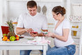 Pregnant family with money family budget and baby s clothes sit in the house kitchen Stock Image