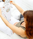 Pregnant female with baby clothes relaxing on sofa Royalty Free Stock Images