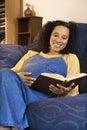 Pregnant female reading. Stock Photos