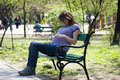 Pregnant girl on a bench Stock Images