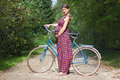 Pregnant girl with bicycle on a forest road, side view Royalty Free Stock Photo