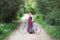 Pregnant girl with bicycle on a forest road, soft focus, side vi Royalty Free Stock Photo