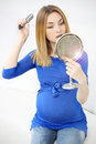 Pregnant girl brushing her hair woman combing looking in the mirror Stock Photo