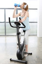 Pregnant girl exercising on a stationary bike to the beat Royalty Free Stock Photo