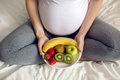 Pregnant girl holding a bowl of fruit Royalty Free Stock Photo
