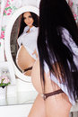 Pregnant girl is looking at her reflection in young woman with long black hair wearing white shirt and standing infrint of mirror Royalty Free Stock Photo