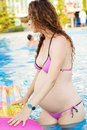 Pregnant girl with mattress in pool Royalty Free Stock Photo