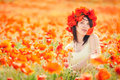 Pregnant happy woman in a flowering poppy field outdoors beautiful wreath summer outdoor portrait Royalty Free Stock Photo