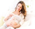 Pregnant happy woman holding baby shoes Royalty Free Stock Photo