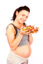 Pregnant healthy food young woman with fruits refers to life Stock Image