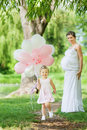 Pregnant mother and her daughter have fun outdoor Royalty Free Stock Photos