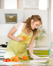Pregnant mother preparing food in kitchen and reading cooking re Stock Image