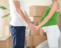 Pregnant wife holding hands of her husband in new home cute standing front boxes during moving Stock Image