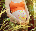 Pregnant woman abdomen with drawing sun Stock Photo