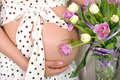 Pregnant woman abdomen with flowers tulips Royalty Free Stock Photography