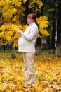 Pregnant woman in autumn park hold maple leaf #1 Royalty Free Stock Images