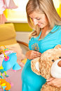 Pregnant woman in baby room Stock Photography