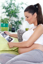 Pregnant woman with baby s ultrasound scan sitting on a sofa looking at her unborn Royalty Free Stock Photo