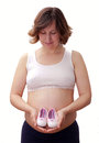 Pregnant woman with baby shoes on her belly mother holding pink Stock Photography