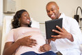 Pregnant woman being given ante natal check by doctor looking at tablet smiling Royalty Free Stock Image