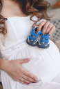 Pregnant woman belly holding baby booties home portrait of by the window at home home cozy portrait of resting at home happiness Royalty Free Stock Images