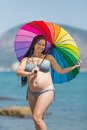 Pregnant woman in bikini with iridescent parasol against sea
