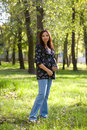Pregnant woman in blue jeans saunter in park Stock Image