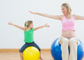 Pregnant woman bouncing on exercise ball with young daughter women in a fitness studio Stock Image